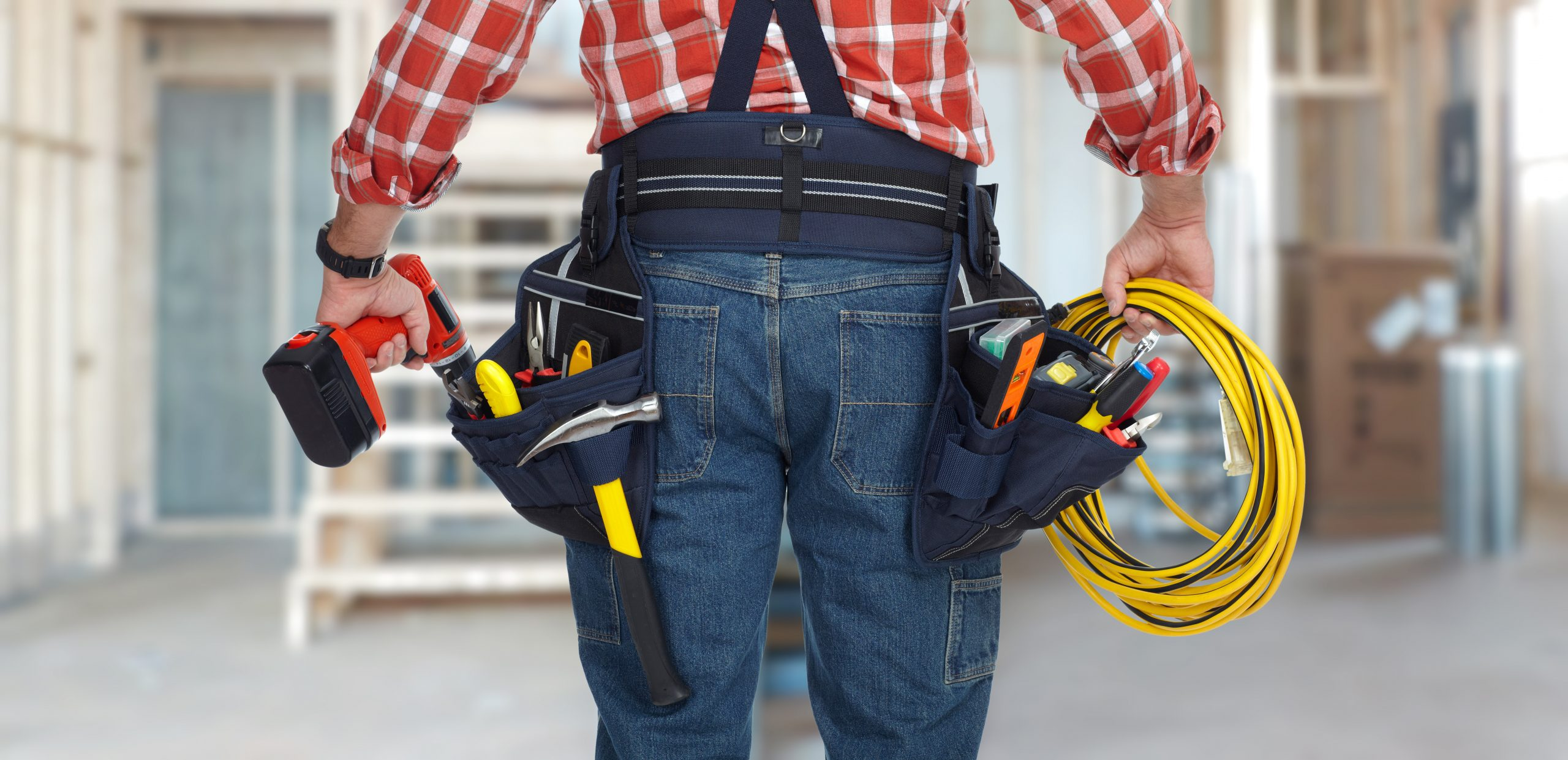 Electrician,Man,With,Drill,And,Wire,Cable,Over,Construction,Background.
